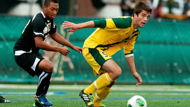 Vermont's Charlie DeFeo (5) gets past UMBC's Malcolm Harris (77) with the ball during a 2013 men's soccer game at Virtue Field.