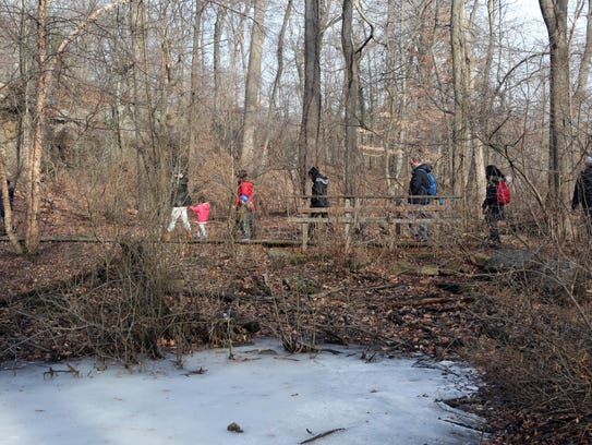 A guided trail walk passes the frozen pond at the Greenburgh