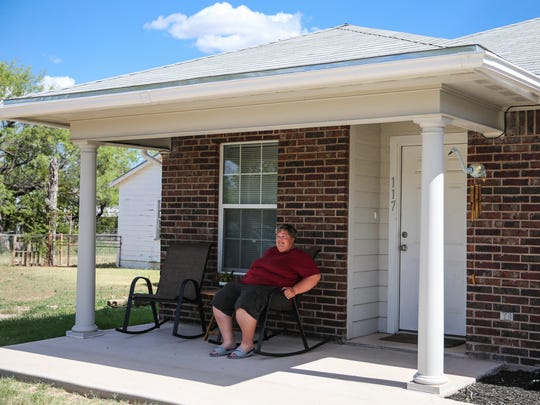Tara Davis sits outside her home Thursday, July 20, in San Angelo. She received help with the purchase of a home through the Galilee Community Development Corp. program in San Angelo.