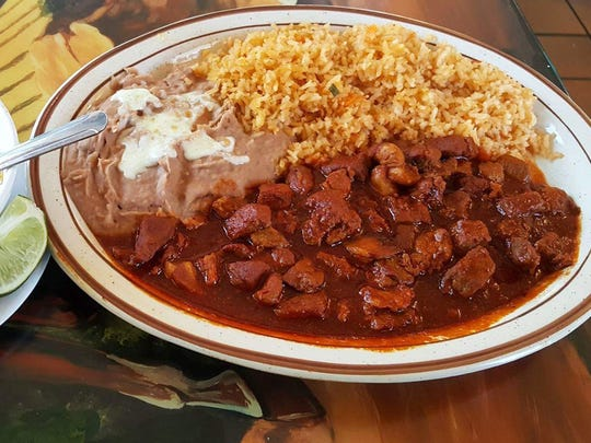 The Asado Delicias ($11), chopped pork meat in red chile sauce with a side of rice, beans and caldo de res.