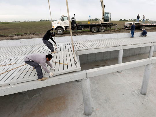 Workers install floor slats at the construction site of Rob Manning's 2,400 head hog confinement building in Dallas County.  Manning says he is building the structure because demand for pork is high and he needs the manure to spread on his fields.