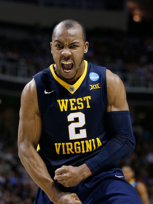 FILE - In this March 23, 2017 file photo, West Virginia guard Jevon Carter (2) celebrates after scoring against Gonzaga during the second half of an NCAA Tournament college basketball regional semifinal game in San Jose, Calif. Carter is the reigning Big 12 defensive player of the year and returns for his senior season in 2017-18.  (AP Photo/Tony Avelar, File)