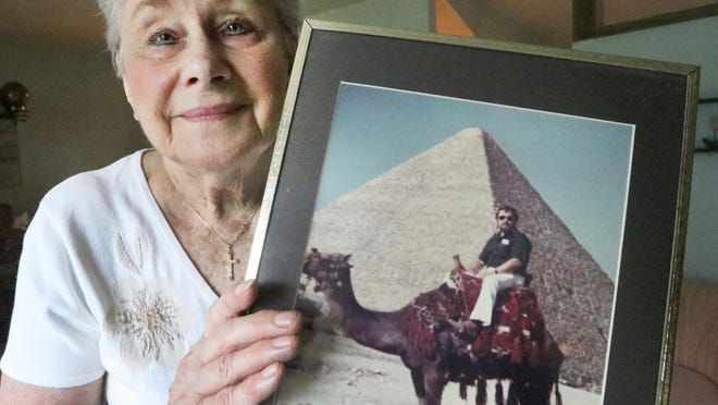 Christine Belter holds a photograph of her husband, Justyn Belter, on a camel, one of the mementos of a life spent traveling the globe. He died on April 8 of coronavirus at age 84.
