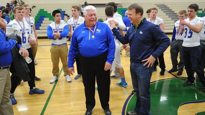 Former Notre Dame Academy Principal John Ravizza, right, congratulates  football coach John Nowak for winning the WIAA Division 3 state football championship in 2015.