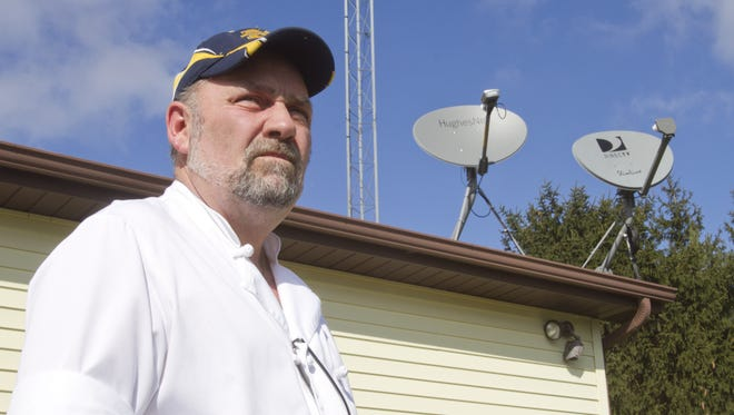 In this photo from March, Conway Township resident Chuck Skwirsk stands near a dish supplied by HughesNet he uses to improve his internet service. He's tried several providers in an effort to get internet service.