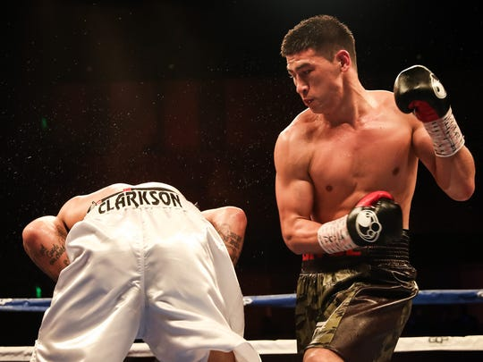 Dmitry Bivol, right, connects with a right to the body of Samuel Clarkson Friday night during their WBA light heavyweight fight. Bivol won by TKO.