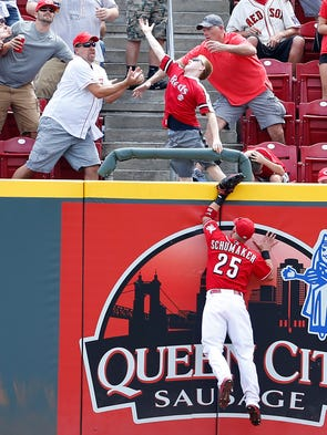 Right fielder Skip Schumaker (25) can't climb the wall on Boston Red Sox first baseman Mike Napoli's (12) home run in the fifth inning at Great American Ball Park.