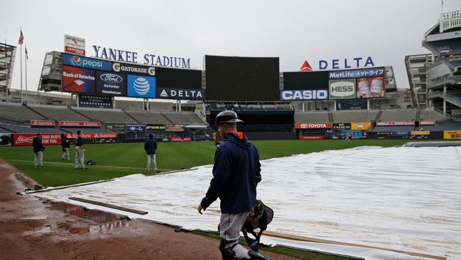 Houston Astros' players work out in a light rain at Yankee Stadium, Monday, April 4, 2016 in New York. The opener between the Houston Astros and the New York Yankees at Yankee Stadium has been postponed because of a forecast of bad weather and rescheduled for Tuesday afternoon.