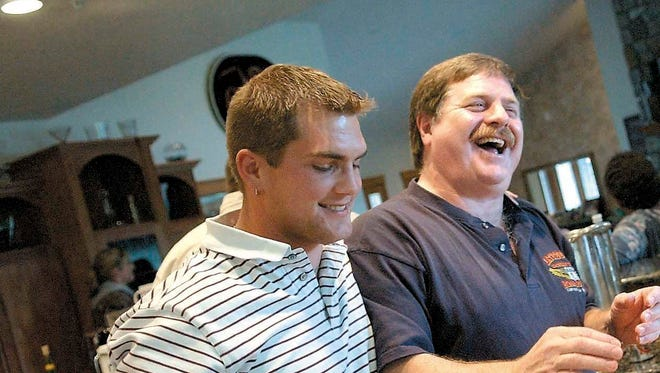 """In this April 18, 2006 file photo, Capt. Rick Quashnick, right, shares a laugh with boat engineer Blake Painter, left, as family and close friends gather at Quashnick's Warrenton, Ore., house to watch the Discovery Channel series """"The Deadliest Catch."""""""