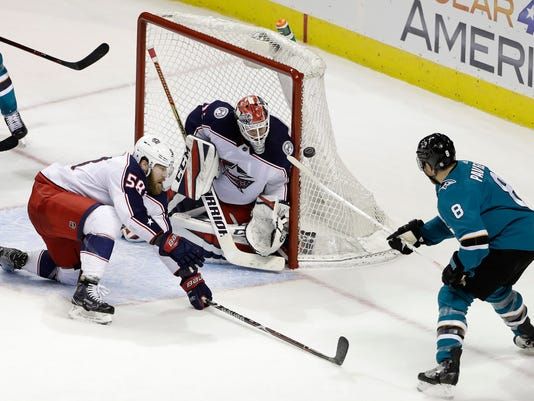 Columbus Blue Jackets goaltender Sergei Bobrovsky, center, stops a shot from San Jose Sharks center Joe Pavelski, right, during the third period of an NHL hockey game, Sunday, March 4, 2018, in San Jose, Calif. Columbus won 4-2. (AP Photo/Marcio Jose Sanchez)