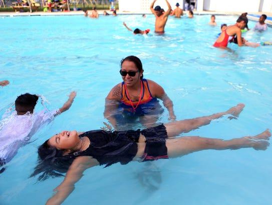 Lifeguard Maggie Vasquez (top) helps Lillyanna Flores,