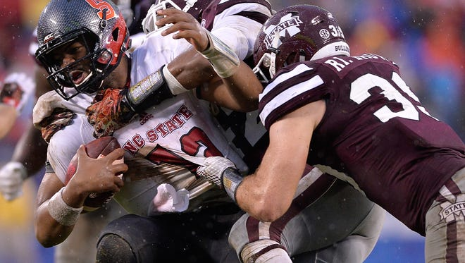 CHARLOTTE, NC - DECEMBER 30: A.J. Jefferson #47 and Richie Brown #39 of the Mississippi State Bulldogs sack Jacoby Brissett #12 of the North Carolina State Wolfpack during the Belk Bowl at Bank of America Stadium on December 30, 2015 in Charlotte, North Carolina.  (Photo by Grant Halverson/Getty Images)