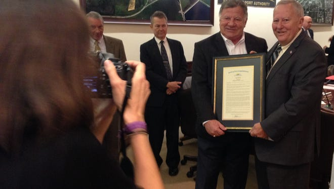 Retiring Lee County Port Authority Executive Director Bob Ball, left, and County Commissioner Frank Mann pose with the resolution commending Ball for his service and achievements at Southwest Florida International and Page Field general aviation airport.