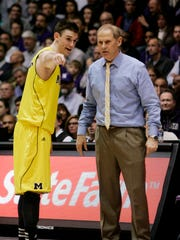 Michigan coach John Beilein talks with guard Stu Douglass during overtime against Northwestern on Feb. 21, 2012 in Evanston, Ill.