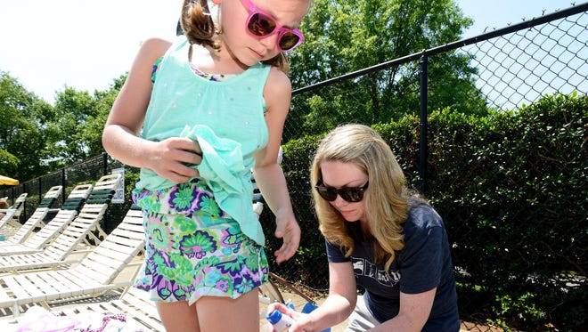 Cortney Easterling puts sunscreen on her daughter Mills, 8, before swimming.