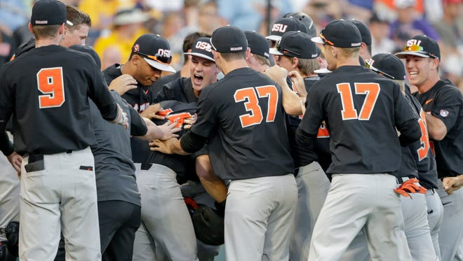 Oregon State's KJ Harrison, in the middle of the pack, is mobbed by celebrating teammates and coach Pat Casey (9) after he hit a grand slam in the sixth inning of an NCAA College World Series baseball game against LSU in Omaha, Neb., Monday, June 19, 2017. Steven Kwan, Michael Gretler, and Trevor Lamach also scored on the play.