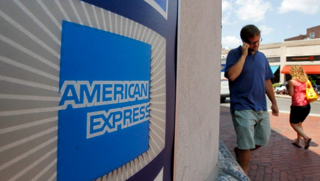 In this July 19, 2011, file photo, passers-by walk past an American Express logo near the entrance to a bank in the Harvard Square neighborhood of Cambridge, Mass.