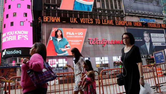 """People walk past a news ticker that reads """"U.K. Votes to Leave European Union,"""" Friday, June 24, 2016, in New York's Times Square. Britain voted to leave the European Union after a bitterly divisive referendum campaign, sending global markets plunging, casting British politics into disarray."""