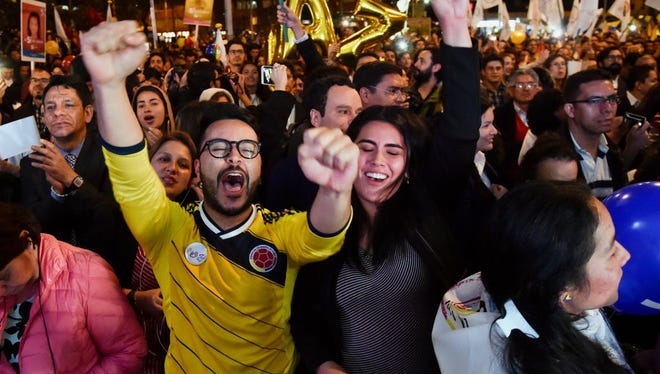 Colombians celebrate as they watch on a giant screen broadcasted from Havana, Cuba, the signing of agreement of conclusion of the peace talks between the Colombian Government and FARC guerrilla, Wednesday in Bogota.