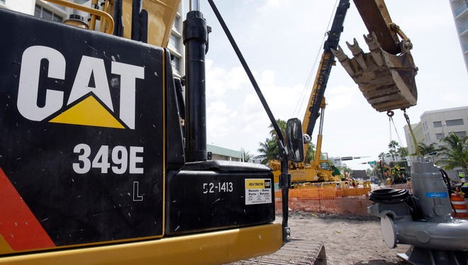 A Caterpillar 349E Hydraulic Excavator operates on a construction site in Miami Beach, Fla. Caterpillar announced that it is moving its global headquarters to the Chicago area.