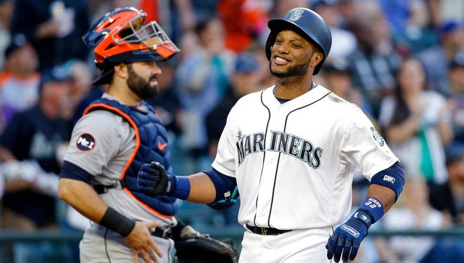 Seattle Mariners' Robinson Cano, right, smiles as he crosses home in front of Detroit Tigers catcher Alex Avila on his two-run home run during the third inning.