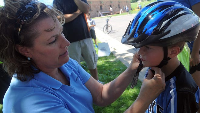 Bradyn LeBarge (right) gets fitted for a bike helmet from Corolla Lauck (right) during Tour Sioux Falls in Falls Park on Sat., June 27, 2015. When buying gifts for the holidays, it's important to keep safety in mind. Bikes should come with helmets if a child doesn't already have one to wear.