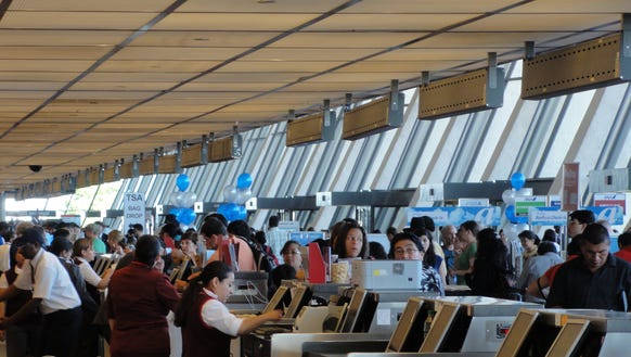 Airline passengers line up at the ticket counters to