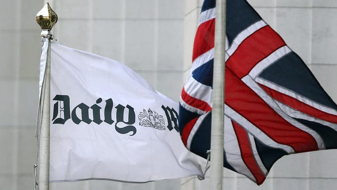 """The Union Jack flag flies beside a flag advertising the """"Daily Mail"""" outside Northcliffe House on Oct. 4, 2013."""