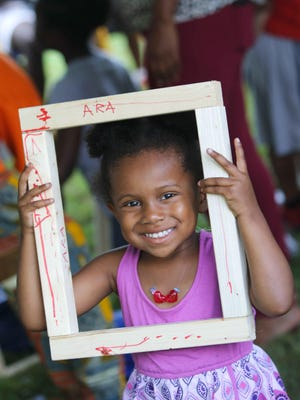 Three-year-old Ara Osimokun uses a drum shell as a picture frame at the Afrikan Festival at Kirkwood Park in Wilmington Saturday.