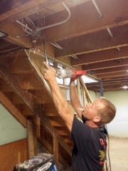 Louis Logan of DC Electric works on making a path for wiring at the 29th and Erie home Wednesday, July 29, in Sheboygan.