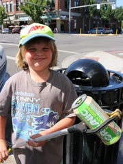 """Spencer Nuss, 7, shows off his """"grabber,"""" which he uses to find cans and bottles in his neighborhood every week. He helps his neighbors sort, cleans up after folks who put the wrong items in the wrong bins, and is waved to by all of the refuse drivers and haulers in his southeast Salem neighborhood."""
