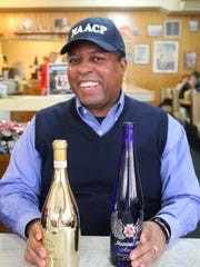 Michael Chenault of the Salem-Keizer NAACP displays one of the dazzling bottles of wine to be auctioned Friday evening, Dec. 11, at the Yost Art Gallery.