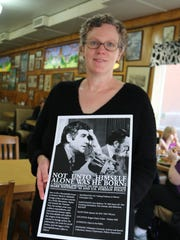 Willamette University archivist Mary McRobinson holds a poster about the roundtable discussion featuring former aides to the late Sen. Mark O. Hatfield.