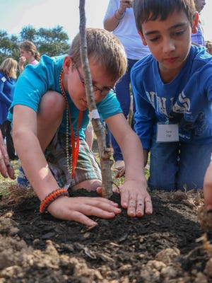 Students from the DuBard School for Language Disorders assist in the planting of an edible orchard at Southern Miss.