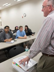 Professor Dennis Fahey, right, introduces students to a case portfolio commonly known as a murder book during the advanced crime scene class at Florida SouthWestern State College in Fort Myers on Jan. 11. The murder book is a binder that contains all pertinent case information, like warrants, autopsy reports, photos and sketches.