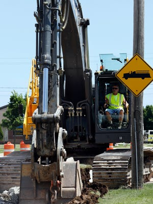 An excavator digs up the pavement and the curb on Dewey Street Tuesday, July 26. The four-lane street has been narrowed to one lane, and eastbound only, as a result of the construction.