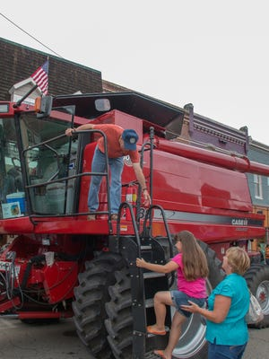 Virgil Shockley, top, helps a child up to see his combine at the annual Blessing of the Combines in Snow Hill. The 2016 event happens Aug. 6.