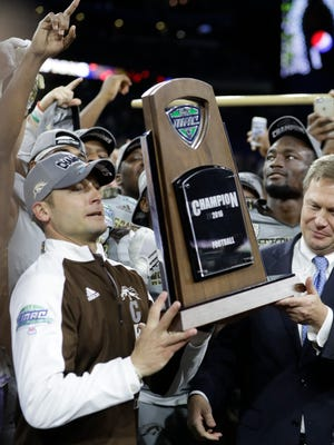 Western Michigan head coach P.J. Fleck is presented the Mid-American Conference championship trophy by Commissioner Dr. Jon Steinbrecher after an NCAA college football game against Ohio, Friday, Dec. 2, 2016, in Detroit.