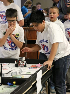 Random Lake Middle School students Tanner Birenbaum, left, and Frankie Hernandez, right, put their Lego-made robot through a competition last month at Lakeshore Technical College. Teammate Rafer Vincent is in the background.