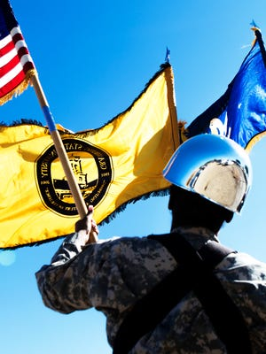 A soldier holds a Grambling State University flag along with the American flag and the Louisiana state flag.
