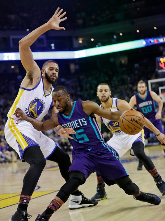 Charlotte Hornets' Kemba Walker, center, is defended by Golden State Warriors' JaVale McGee, left, during the first half of an NBA basketball game Wednesday, Feb. 1, 2017, in Oakland, Calif. (AP Photo/Marcio Jose Sanchez)