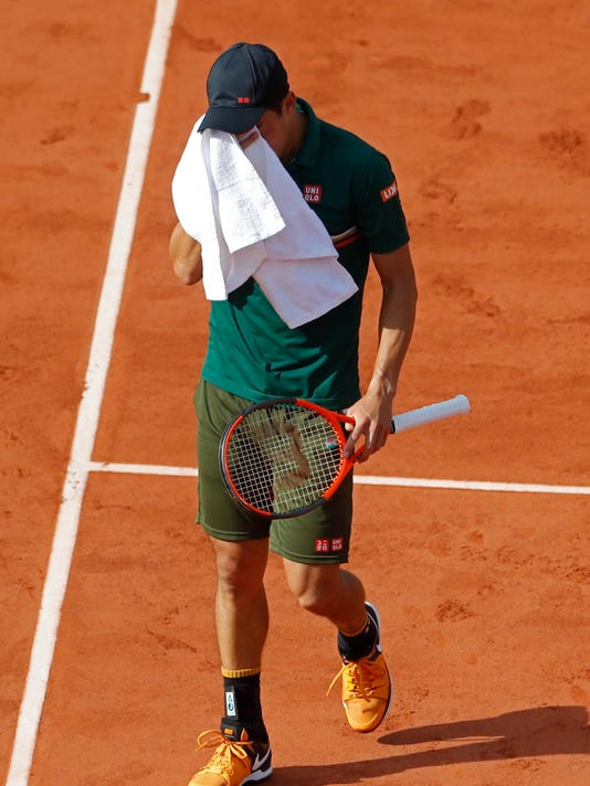 Japan's Kei Nishikori wipes the sweat off his face during his quarterfinal match of the French Open tennis tournament against Britain's Andy Murray at the Roland Garros stadium, in Paris, France. Wednesday, June 7, 2017. (AP Photo/Petr David Josek)