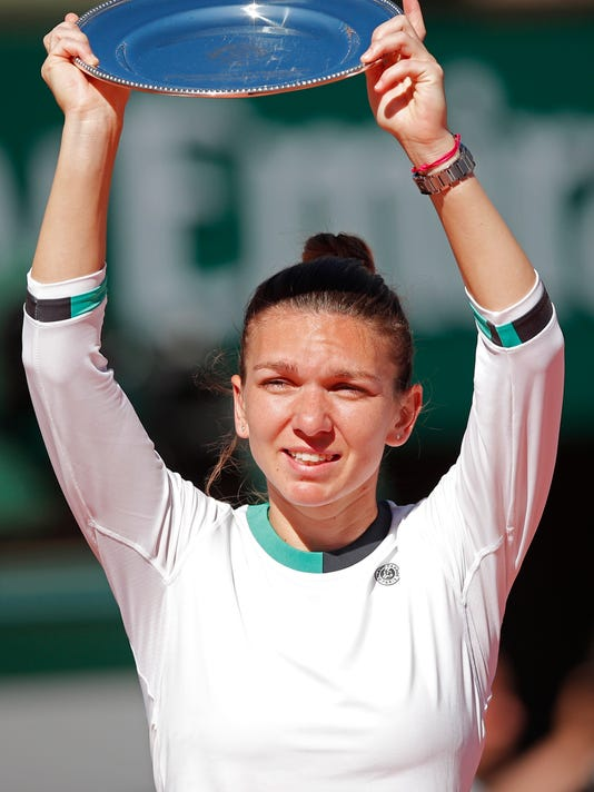 Romania's Simona Halep holds the runner-up trophy after losing to Latvia's Jelena Ostapenko in the women's final match of the French Open tennis tournament at the Roland Garros stadium, in Paris, France, Saturday, June 10, 2017. (AP Photo/Christophe Ena)