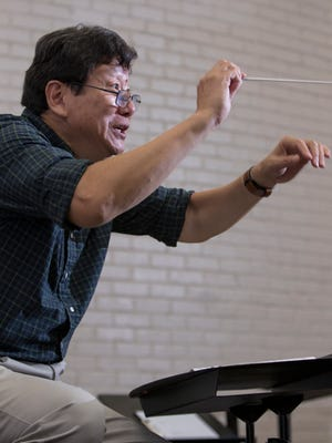 Artistic Director Xiaolun Chen conducts the Choral Society of Pensacola during rehearsal Monday, Oct. 9, 2017, at Pensacola State College. Chen is celebrating 20 years with the organization this season.