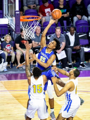 McEachern's Isaac Okoro gets the basket on Simeon players Messiah Jones and Talen Horton-Tucker. Simeon played McEachern in the City of Palms third-place game Saturday, December 23, 2017.