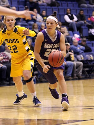 Mariah Szymanski of USF dribbles around the defense of Lynsey Prosser of Augustana during Friday night's game at the Arena.