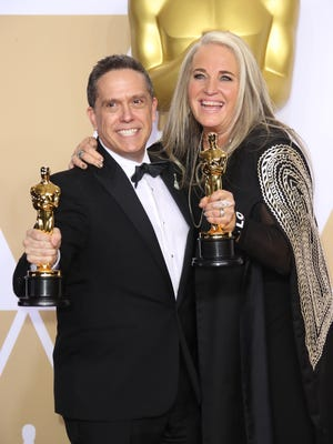 'Coco' director Lee Unkrich, left, and producer Darla K. Anderson show off their Oscar statuettes after winning for best animated feature film.