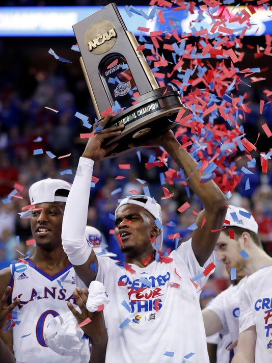 Kansas' Lagerald Vick holds the trophy along side teammate Marcus Garrett after defeating Duke 85-81 in overtime of a regional final game in the NCAA men's college basketball tournament Sunday, March 25, 2018, in Omaha, Neb. (AP Photo/Charlie Neibergall)