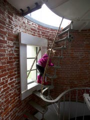 Lucy Urness, 3, climbs up a narrow staircase into the