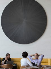 Cafe patrons socialize in front of a tondo created by Michelle Grabner at Northwestern Mutual in downtown Milwaukee.